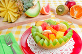 Fresh fruit salad with kiwi, banana, peach, orange, red orange, apricot and melon in handmade melon bowl.Fresh fruits in the background.