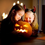 Two pretty young sisters in halloween costumes carving a pumpkin together