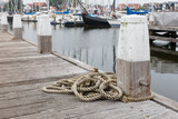 Wooden pier with bollard and rope in Dutch harbor Urk