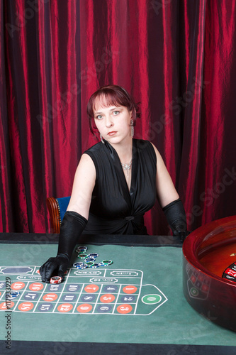 Plakat sexy woman wearing black dress and black gloves plays in a casino