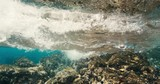 Underwater view of tropical coral reef and breaking waves