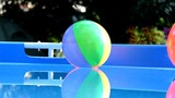 Colorful beach balls floating in a pool.