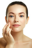 Daily makeup. Beauty concept. Young woman with drops of cream on her beautiful face on white background. Healthy and spa. Natural beauty. Woman applying cosmetic cream on her pretty face