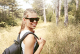 Smiling woman tourist with backpack traveling on the nature. Concept of hiking, camping and recreation.