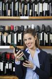 Happy Woman Holding Wine Bottle In Supermarket