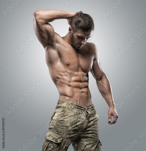Poster Muscular athlete bodybuilder man on a gray background