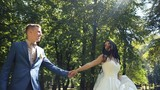 Happy bride walking holding a dress in one arm and grooms hand in another, outdoors