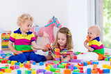 Fototapety Kids playing with colorful toy blocks