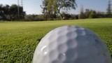 Macro of golf ball being hit into hole.