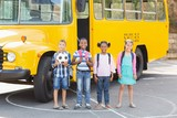 Smiling kids standing together in front of school bus