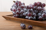 Fresh grapes on wood. Autumn fruit.
