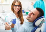 Female dentists examining and working on young male patient.Dentist's office.