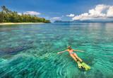 woman snorkelling in tropical waters near island
