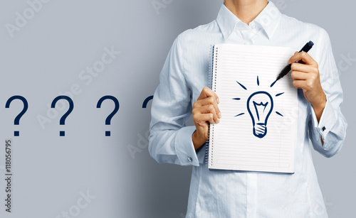 Fototapeta Searching for Ideas. Woman holding notepad with drawing of a bulb standing in front of a wall with a series of question marks