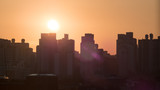 Cityscape in early morning. Building outlines against the warm orange sky and the bright sunshine. Seoul, South Korea