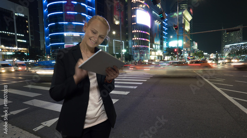 Young woman using touch pad on the busy street of night Seoul city in Republic of Korea. Illuminated buildings, motorway with car traffic and pedestrian crossing in background