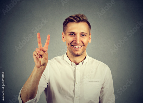 Poster young handsome man holding up peace victory, two sign