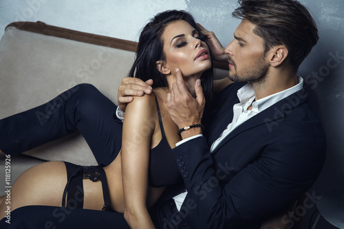 Sexy couple on coach Poster
