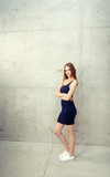 Young woman standing - wall surrounding her for copy space