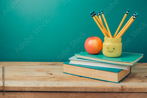 Poster Back to school concept with books, pencils in emoji jar and apple on wooden tabl