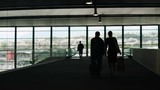 Silhouette of couple carrying luggage in airport hall, tourism, business trip