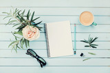 Morning coffee cup, clean notebook, pencil, eyeglasses and vintage rose flower in vase on blue rustic table top view. Planning and design concept. Cozy breakfast. Flat lay styling.