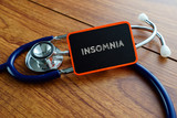 Medical concept.Word INSOMNIA with stethoscope on wooden table.