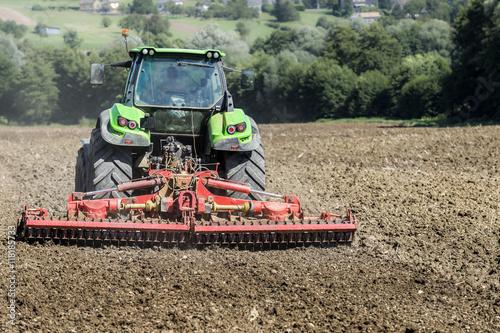 Fotobehang Trekker tracteur passant la herse sur champ labouré
