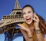 woman talking on mobile phone in front of Eiffel tower, Paris