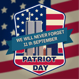 Patriot day badge emblem with buildings and American flag.