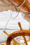 Wooden wheel on a big sailboat at sea. Close up nautical detail