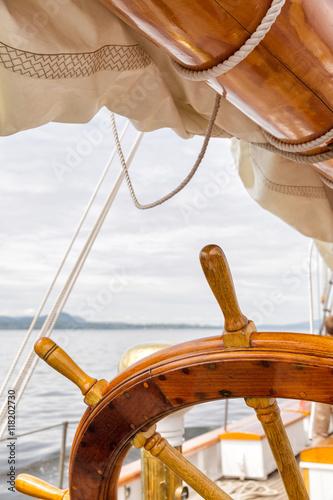 Wooden wheel on a big sailboat at sea. Close up nautical detail Poster