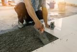 Workers use tile work equipment, renovation - handyman laying ti - 118222306