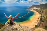 man sitting on the edge of a cliff, enjoying view of Playa de La