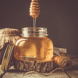 Golden honey in glass jar with dipper