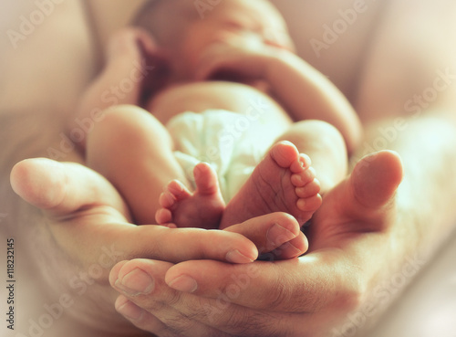 sleeping newborn baby on male hands