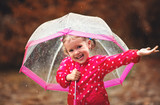 happy child girl laughing with an umbrella in rain