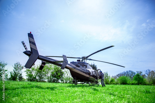 Black with gray stripes bell 407 helicopter standing on green grass field getting ready to fly over blue sky