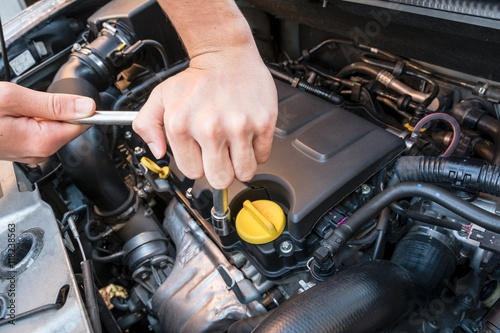 Hands repairing a modern car engine with a wrench Poster