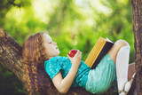 Little girl lying on large tree and reads the book.