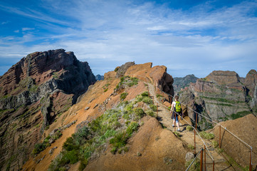 Woman hiker with green backpack is walking to Pico Ruivo hike