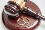 Divorce concept. Closeup view on gavel and wedding rings.