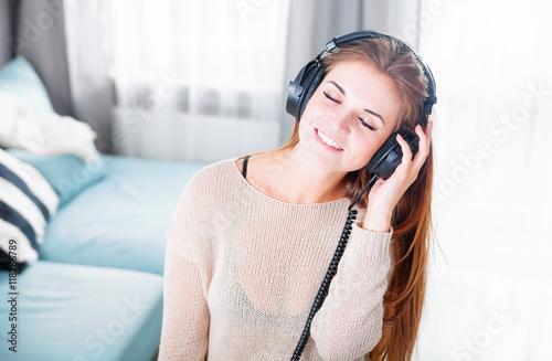 Fotobehang Muziek Woman with headphones listening to music at home