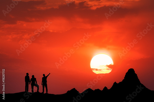 Fotobehang Rood Landscape with silhouette of standing people and beautiful sky with big sun. Friends on the high mountain peak against the beautiful sunset. High rocks. Travel, Climbing, Trekking.