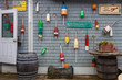 Coastal iconic northeastern USA items including lobster buoys, seafood signs, lobster traps and barrels on shingled building with door open
