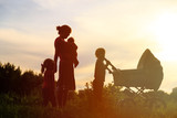 Silhouette of mother with three kids walking at sunset, happy family