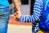 Mother holding hand of little son with backpack, back to school
