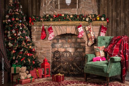 Новогодние или Рождественские декорации, кресло с пледом рядом с камином и нарядной елкой