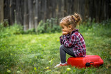 little girl sitting on red canister, a sad emotion