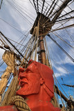 Carved head of sailor painted in a fiery orange red and rigging ropes at foredeck of Tall Ship HMB Endeavour at Darling Harbour in Sydney, Australia